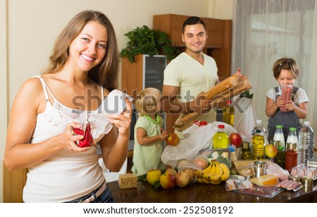Middle-class family of four with bags of food at home  - stock photo