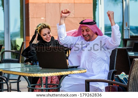 Middle Eastern Arabic couple work with lap top outdoor. - stock photo