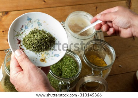 Middle Eastern cuisine: chef mixing spices and herbs to give flavour to the food. On the plate is dried parsley, the chef is dipping into the powdered garlic jar. - stock photo