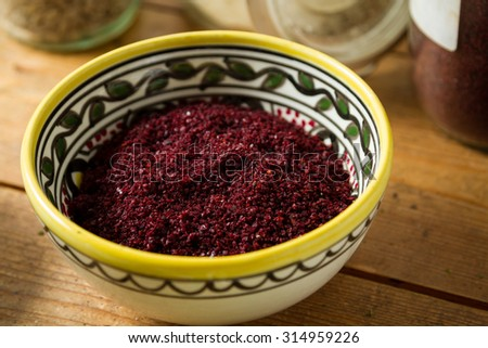 Middle Eastern cuisine: close-up on bowl of sumac. Sumac powder is used in Arabic cuisine to add zest and flavour to dishes. Jars of ginger and parsley and other herbs in the background. - stock photo