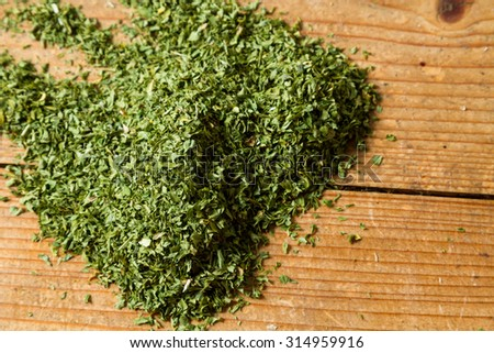 Middle Eastern cuisine: dried parsley on wooden background. - stock photo