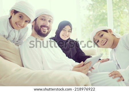 Middle eastern family at home on couch using tablet