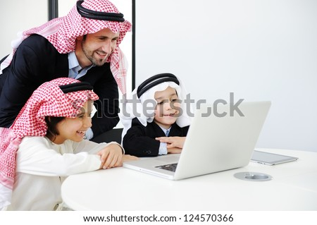 Middle eastern father with sons working on laptop - stock photo