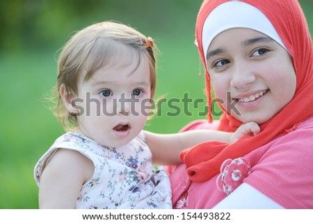 Middle eastern female with little baby playing in summer grass - stock photo