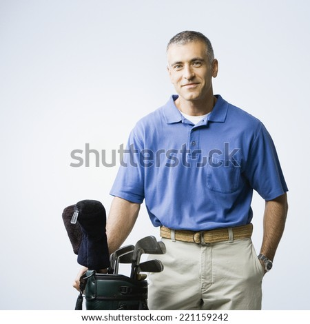Middle Eastern man next to golf bag - stock photo