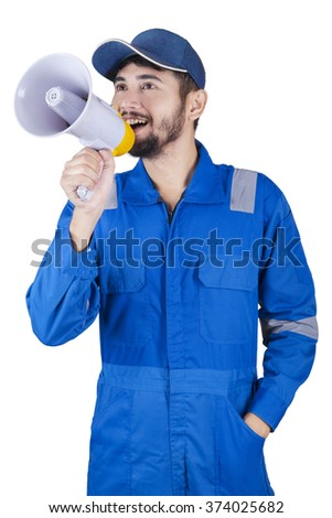 Middle eastern mechanic using a megaphone to announce information while wearing uniform in the studio - stock photo