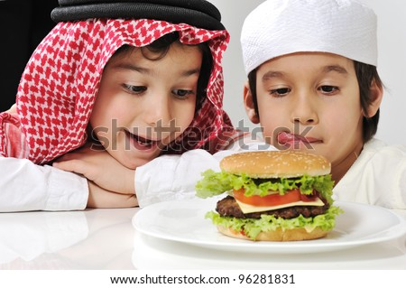 Middle eastern two little kids with big Burger - stock photo
