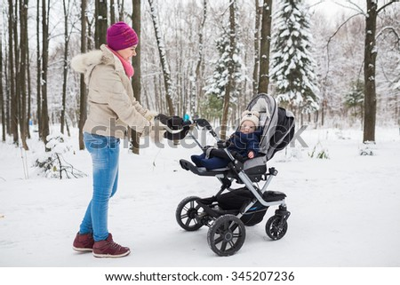 Middle eastern woman with stroller going for a walk in a park during lovely winter afternoon