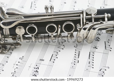 Middle of a clarinet with keys lying across some sheet music