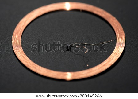 middle RFID Antenna copper coil black background - stock photo