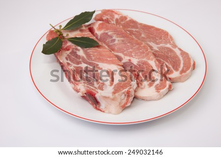 Middle rib chops of pork over plate. Isolated on white with bay - stock photo