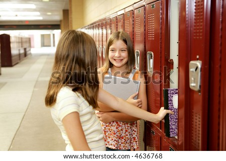 Middle school girls gossiping at their lockers. - stock photo