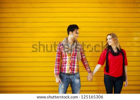 Middle shot of a young couple looking at each other and holding hands - stock photo