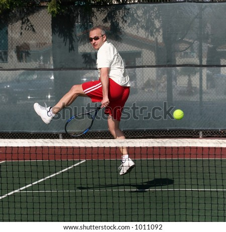 Middleage man playing tennis - stock photo