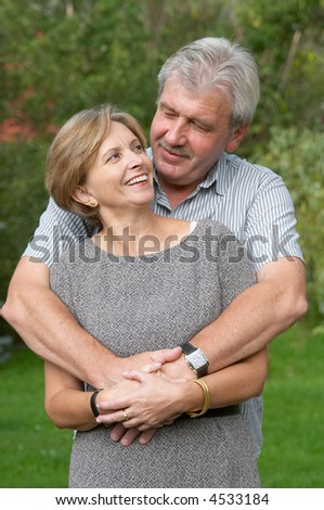 Middleaged couple smiling to each other. - stock photo
