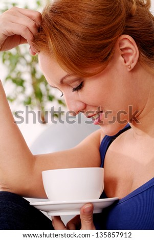 Middleaged happy woman enjoy her morning cup of tea at home - stock photo