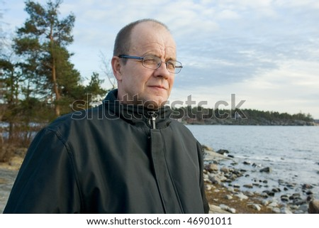 Middleaged man standing by the sea - stock photo