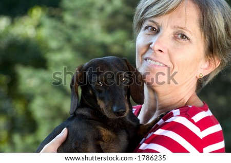 Middleaged woman holding a dog. Focus on woman's face. - stock photo