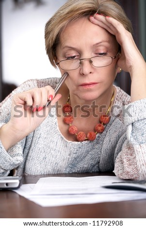 Middleaged woman sitting over the documents - stock photo