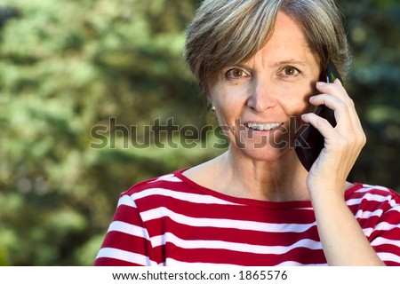 Middleaged woman talks on the mobile phone - stock photo