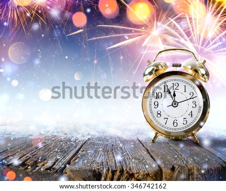 Midnight Celebration - Clock On Snowy Table With Fireworks - stock photo