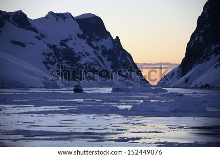 Midnight sun (at 3am) in the Lamaire Channel on the Antarctic Peninsula in Antarctica. - stock photo
