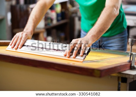 Midsection mid adult worker using squeegee in factory - stock photo