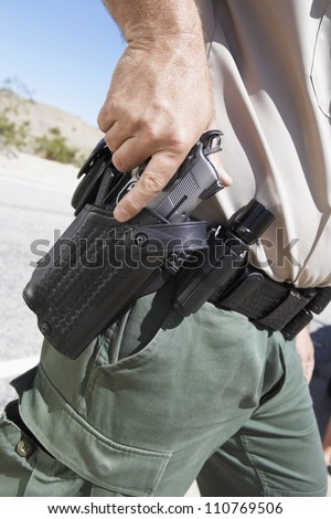 Midsection of a policeman holding gun - stock photo