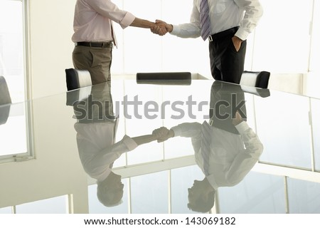 Midsection of business people shaking hands in conference room - stock photo