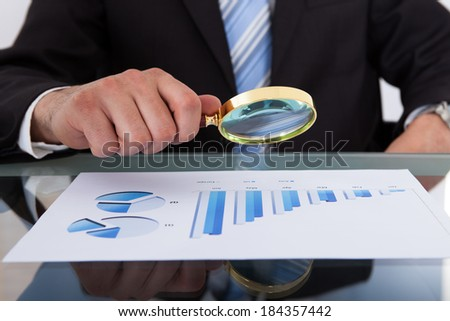 Midsection of businessman analyzing bar graph through magnifying glass in office - stock photo