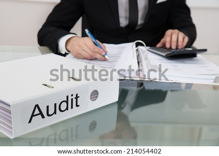 Midsection of businessman calculating taxes with audit folder at desk in office