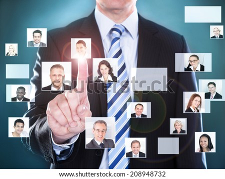 Midsection of businessman choosing the perfect candidate for the job - stock photo