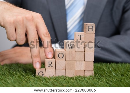 Midsection of businessman climbing growth blocks with fingers on grass - stock photo