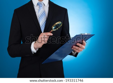 Midsection of businessman examining document on clipboard with magnifying glass against blue background - stock photo