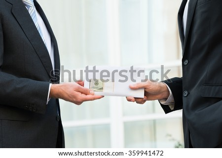 Midsection of businessman giving bribe to partner outdoors - stock photo