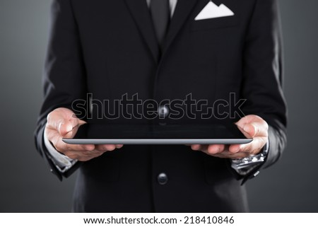 Midsection of businessman holding digital tablet over gray background - stock photo