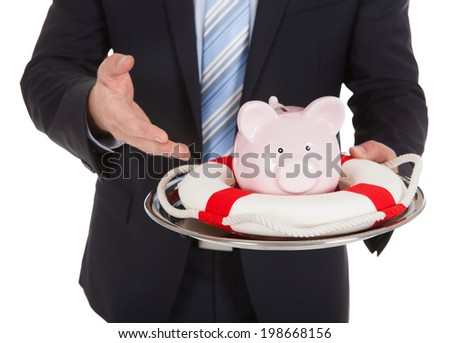Midsection of businessman protecting piggybank with lifebuoy over white background