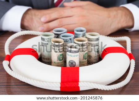 Midsection of businessman protecting rolled bank notes with lifebuoy on table - stock photo