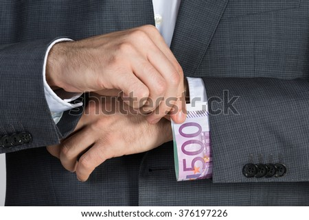 Midsection of businessman putting bribe in suit sleeve at office