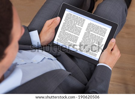 Midsection of businessman reading eBook in office
