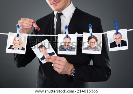 Midsection of businessman selecting candidate from clothesline against gray background - stock photo