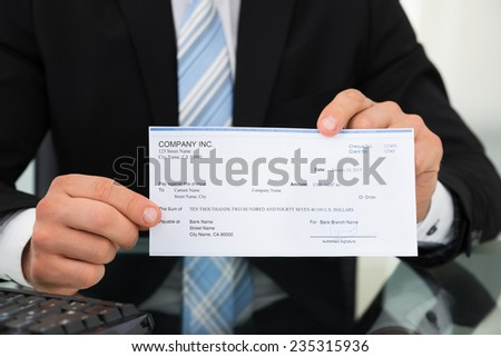 Midsection of businessman showing cheque at desk in office - stock photo