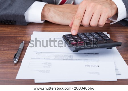 Midsection of businessman using calculator on invoice documents at office desk