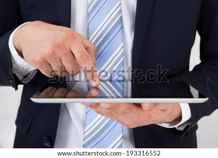 Midsection of businessman using digital tablet in office - stock photo
