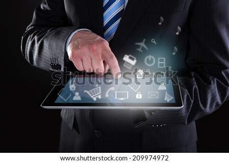 Midsection of businessman using digital tablet with various icons over black background - stock photo