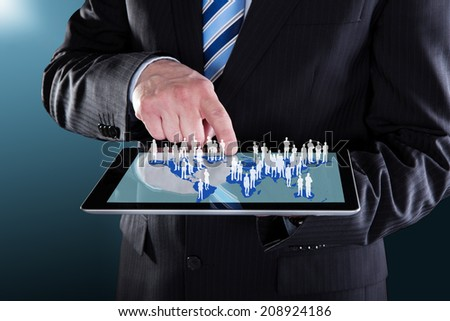 Midsection of businessman using digital tablet with world map representing globalization. - stock photo