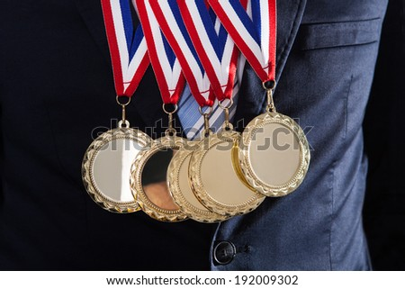 Midsection of businessman wearing gold medals against black background