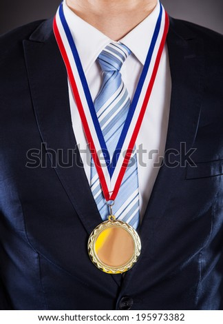 Midsection of businessman wearing medal against black background - stock photo
