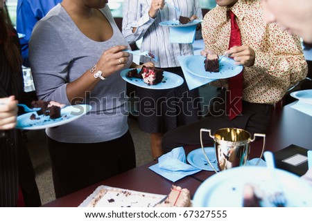 Midsection of businesspeople eating cake - stock photo