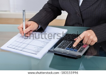 Midsection of businesswoman calculating tax at desk in office - stock photo
